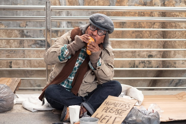 Mendicante senzatetto sporco invecchiato che mangia pane sul ponte