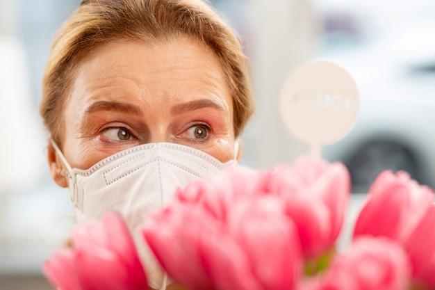 Casalinga anziana che indossa una maschera con forte allergia e si sente sensibile ai fiori