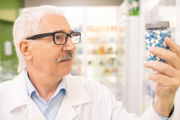 Maschio invecchiato farmacista o consulente di una grande farmacia contemporanea guardando il barattolo con pillole o additivi biologicamente attivi in mano