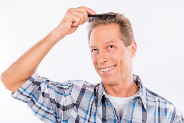 Uomo invecchiato che pettina i suoi capelli