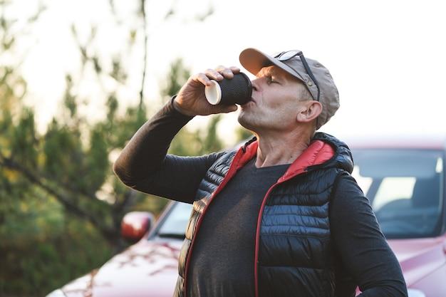 Un uomo anziano beve una bevanda calda da una tazza usa e getta nella foresta