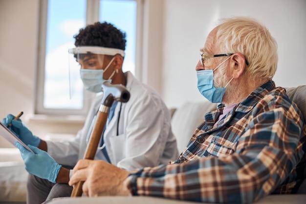 Uomo anziano con una maschera che guarda un dottore