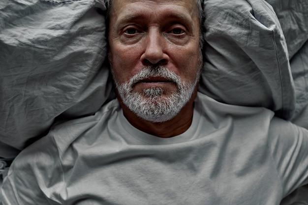 Uomo in pensione invecchiato sdraiato a letto con gli occhi aperti, avendo problemi con il sonno. nonno anziano maturo infelice che soffre di insonnia durante la notte.