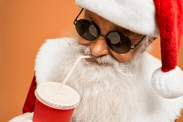Babbo natale invecchiato in occhiali da sole con bevanda gassata in bicchiere di carta