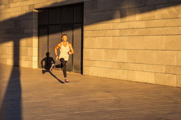 Sportivo invecchiato che corre sulla strada di campagna