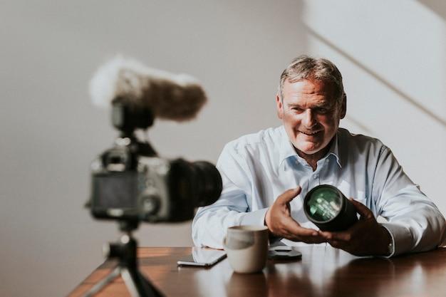 Vlogger invecchiato che registra contenuti sull'obiettivo della fotocamera digitale