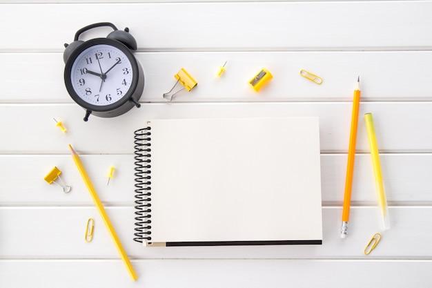 Tavolo da scrivania in legno bianco invecchiato con sveglia vintage nera, blocco note e matite gialle, disposizione piatta