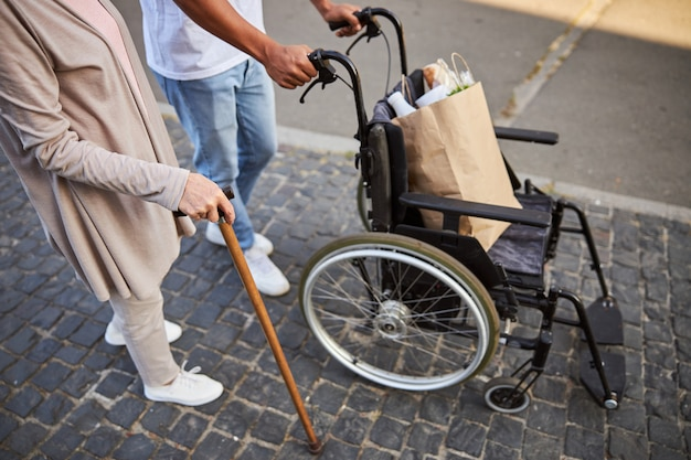 Una donna anziana appoggiata a un bastone da passeggio e un uomo al suo fianco che spinge una sedia a rotelle