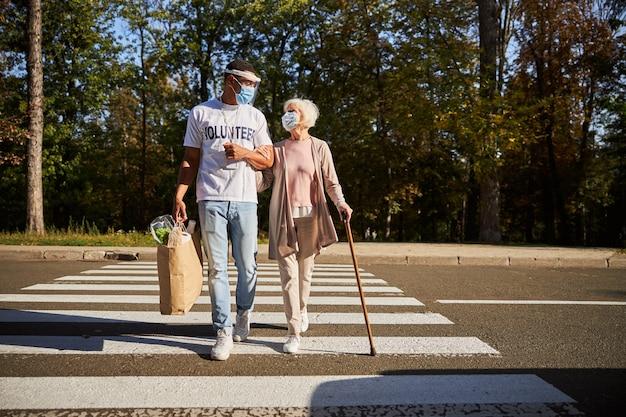 Donna anziana in maschera medica che usa un bastone da passeggio mentre attraversa la strada con una giovane volontaria che porta la sua borsa della spesa