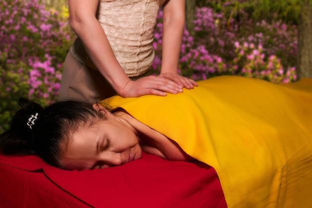 Una donna anziana riceve un massaggio alla schiena da un massaggiatore privato