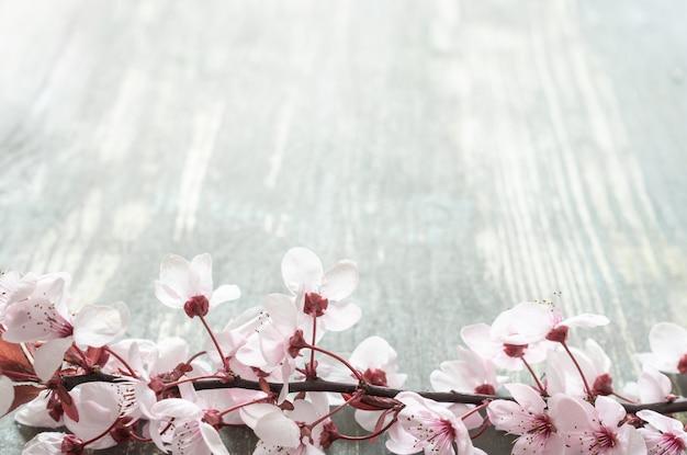 Tavolo in legno invecchiato con un ramo pieno di fiori rosa