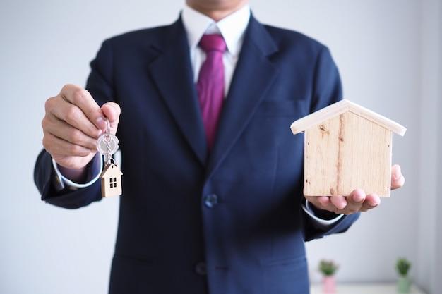 Agenzia che vende casa con una nuova chiave di casa. vendite di case e attività di noleggio e acquisto di assicurazioni