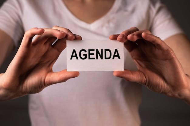 Parola di ordine del giorno su carta in mani femminili. concetto di riunione e pianificazione.