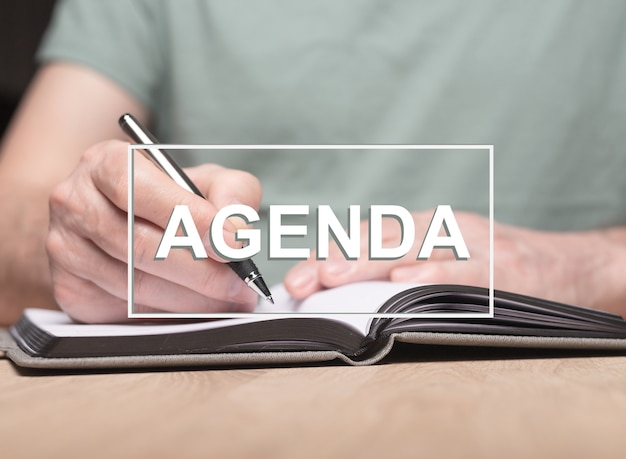 Parola di agenda con foto di mani maschili che scrivono in pianificatore o organizzatore.