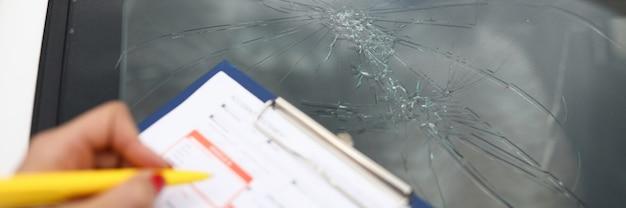 L'agente redige i documenti per il parabrezza rotto in auto. servizi del concetto di compagnie di assicurazione