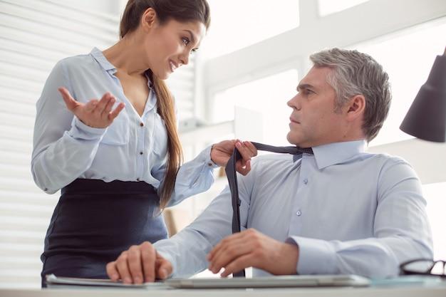 Comportamento aggressivo. bella donna attraente piacevole guardando il suo collega e parlando con lui mentre si tiene la cravatta