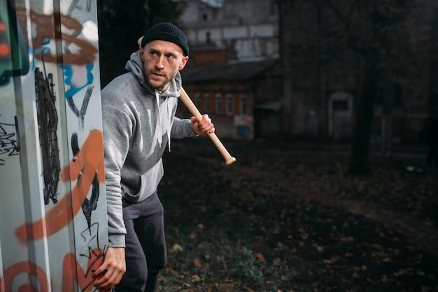 Il ladro maschio aggressivo con la mazza da baseball colpisce la paura. bandito di strada in attesa di vittima. concetto di criminalità, pericolo di attacco di rapina