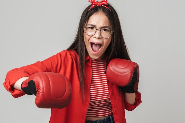 Adolescente aggressiva che indossa abiti casual in piedi isolati su un muro grigio, indossando guanti da boxe, boxe