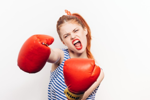 Donna aggressiva in guanti di wrestling rossi su uno sfondo chiaro spalancata la bocca vista ritagliata