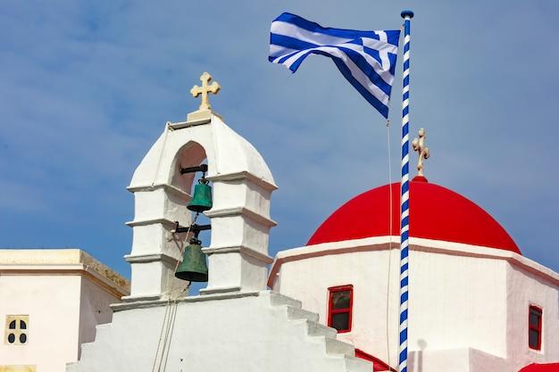 Chiesa di agia kyriaki, tipico edificio bianco della chiesa greca con cupola rossa e grande sventola bandiera greca contro il cielo blu sull'isola di mykonos, grecia
