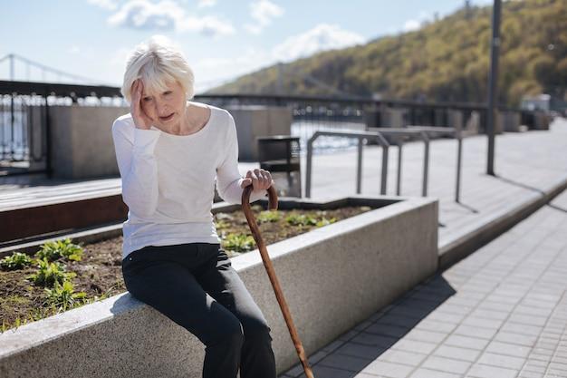 Invecchiamento triste donna stanca che tiene la mano sulla testa mentre esprime emozioni negative e riposa in panchina