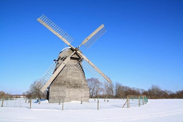 Mulino a vento di invecchiamento sul campo invernale Foto Premium