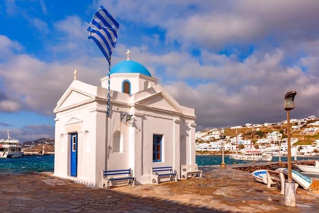 Chiesa cristiana di agios nikolaos, edificio tipico della chiesa greca e grande bandiera greca sventolante nel vecchio porto della città di mykonos, chora, sull'isola di mykonos, l'isola dei venti, grecia