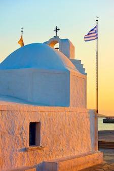 Chiesa greco-ortodossa di agios nikolaos nel porto dell'isola di egina al tramonto, greece