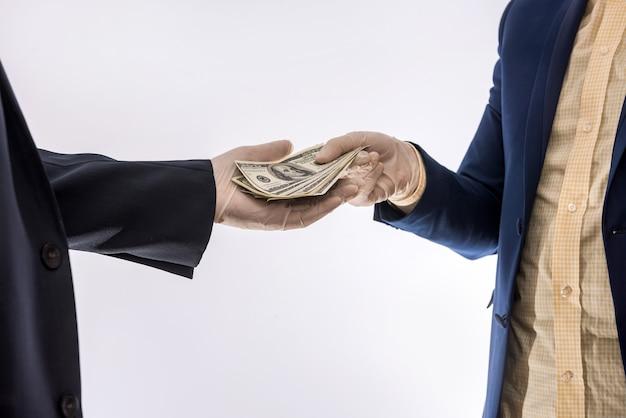 Accordo tra due uomini d'affari durante il periodo del coronavirus, un uomo in guanti dà soldi a un altro uomo d'affari. concetto di sicurezza
