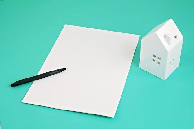 Accordo in attesa di firma, casa e penna su sfondo acquamarina. prestito, assicurazione, concetto di affitto