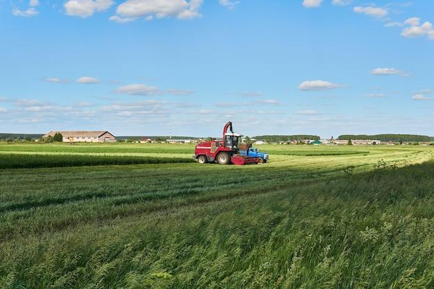 Paesaggio agricolo con una mietitrebbia che raccoglie il raccolto e lo carica sul camion