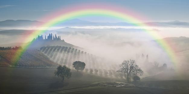 Paesaggio agricolo con arcobaleno e giardino nella nebbia