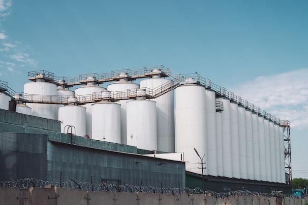 Silos agricoli. conservazione e essiccazione di cereali, grano, mais, soia, girasole. esterno di un edificio industriale. primo piano di grandi contenitori metallici d'argento.