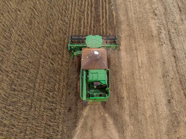 Trattore agricolo che raccoglie semi di soia nel campo.