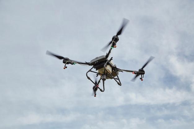 Drone agricolo vola su fertilizzante spruzzato usando drone ai intelligenza artificiale, apprendimento automatico, gemello digitale, 5g, big data, iot, realtà virtuale mista aumentata, ar, vr, robot