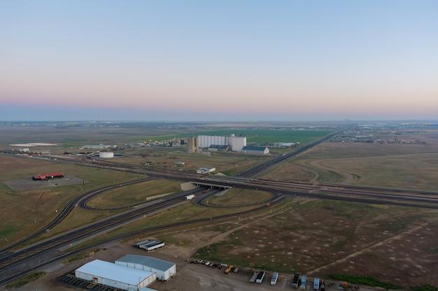 Silos di lavorazione dell'ascensore dell'impianto agricolo per l'essiccazione, pulizia, stoccaggio vicino allo svincolo autostradale con il traffico su un ponte di cereali per prodotti agricoli negli stati uniti