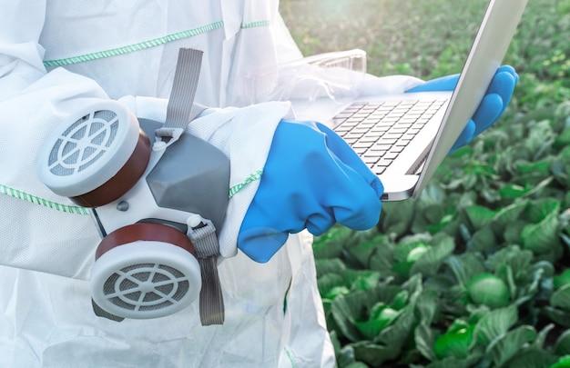 Un agronomo vestito con una tuta protettiva bianca, maschera e guanti blu tiene il portatile contro il campo