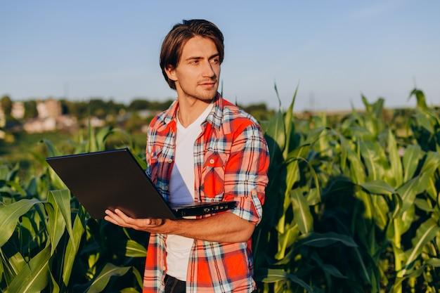 Agronomo che sta in un campo che tiene computer portatile aperto e che sorride e che guarda fuori