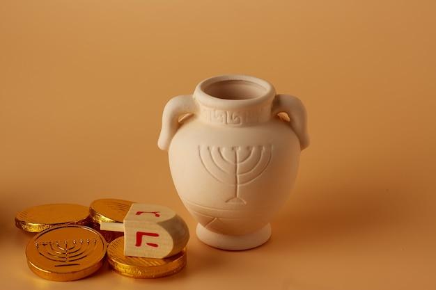 Ah gelt o denaro o monete con hanukkah dreidel e un hanukkah brocca di argilla traduzione buone feste p