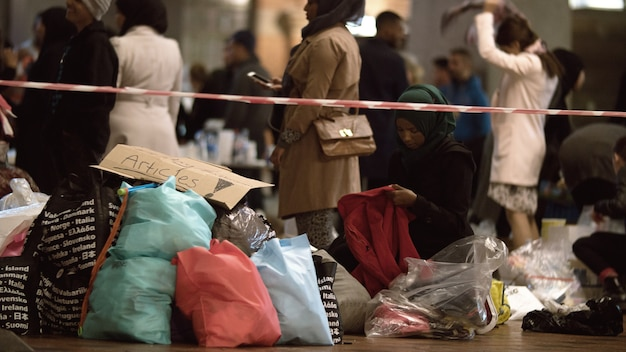 Lavoratore di aiuti che distribuisce vestiti al punto di raccolta di beneficenza nella stazione ferroviaria di copenaghen
