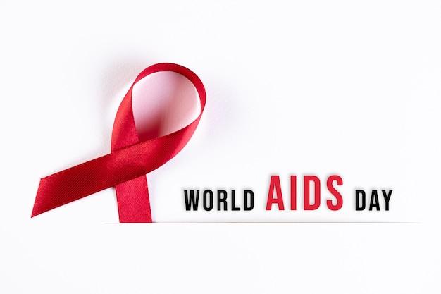 Nastro rosso di consapevolezza dell'aids su carta bianca con testo. concetto di giornata mondiale contro l'aids.