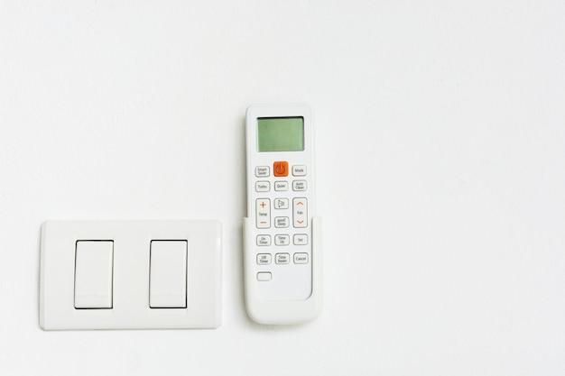 Aria condizionata e interruttore della luce su sfondo bianco con spazio di copia