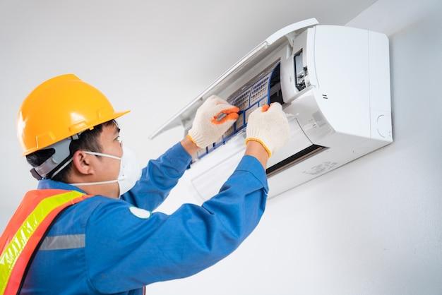 Il tecnico del condizionatore d'aria indossa una maschera di sicurezza per evitare che il tecnico della polvere stia tirando un filtro polveroso dal condizionatore d'aria per pulire il condizionatore d'aria all'interno.