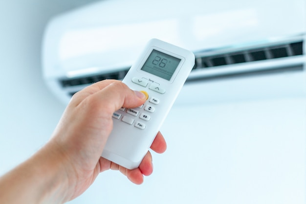 Regolazione della temperatura del condizionatore d'aria con telecomando nella stanza di casa. Foto Premium