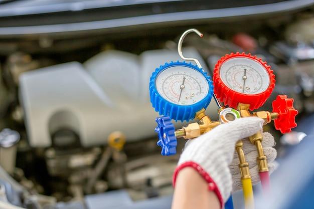 Riparazione dell'aria condizionata, riparatore che tiene in mano lo strumento di monitoraggio per controllare e riparare il sistema di condizionamento dell'aria dell'auto, il tecnico controlla la ricarica del refrigerante del sistema di aria condizionata dell'auto