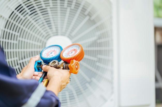 Tecnico dell'aria condizionata e una parte della preparazione per l'installazione del nuovo condizionatore d'aria.