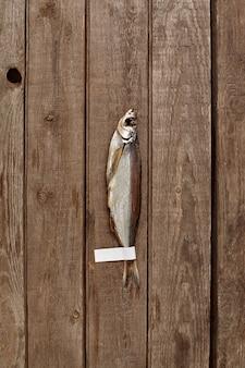Pesce spada essiccato all'aria con etichetta sulla coda su fondo in legno