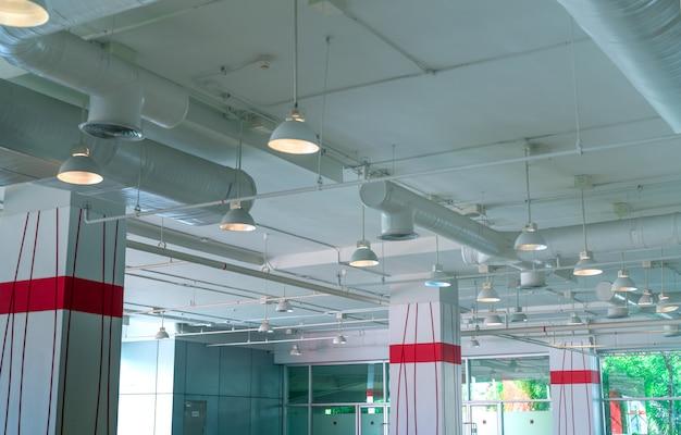 Condotto dell'aria, tubo del condizionatore d'aria, sistema antincendio. flusso d'aria e sistema di ventilazione. costruzione di interni. lampada da soffitto a luce aperta. architettura interiore.
