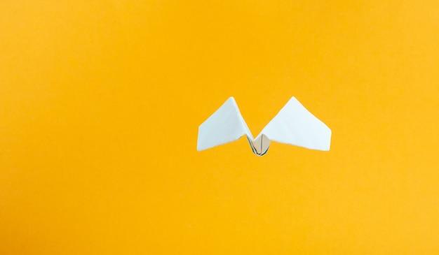 Concetto di mockup di voli aerei, aeroplano di carta blu su uno spazio di copia di sfondo giallo.
