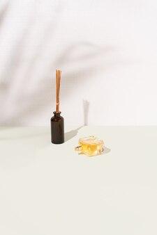 Bastoncini deodorante per ambienti e profumo dorato su sfondo verde pastello e bianco. ombre di foglie di palma. concetto minimo di prodotti per la casa o la bellezza.